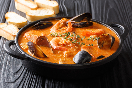 Seafood spicy soup with potatoes, shrimps, mussels, herbs and fish from a picad closeup in a pan served with toast. horizontal Фото со стока