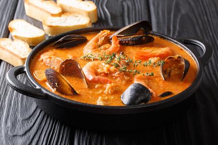 Soupe épicée aux fruits de mer avec pommes de terre, crevettes, moules, herbes et poisson d'un gros plan de picad dans une casserole servie avec du pain grillé. horizontal