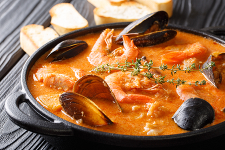 The rich taste of seafood Suquet de Peix soup with potatoes, herbs and fish with the addition of picada close-up in a saucepan on the table. horizontal