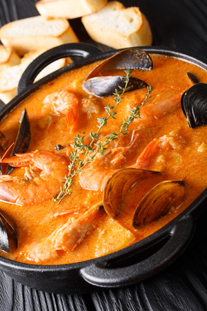Suquet de Peix soup with seafood, potatoes, herbs and fish with seasoned picada close-up in a pan on the table. vertical Stock Photo
