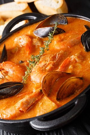 Spanish Suquet de Peix soup with seafood, potatoes, herbs and fish close-up in a pan on the table. vertical
