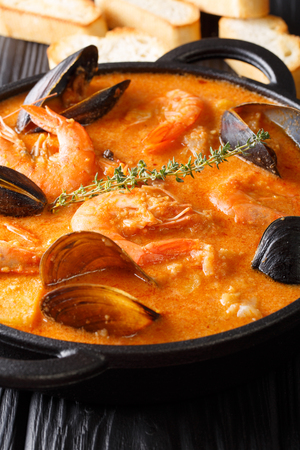 Traditional Catalan recipe: Suquet de Peix Seafood soup, vegetables and fish closeup in a pan served with toasts on the table. Vertical