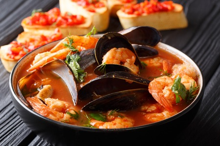 French seafood bouillabaisse soup closeup in a bowl served with toast on the table. horizontal Banque d'images