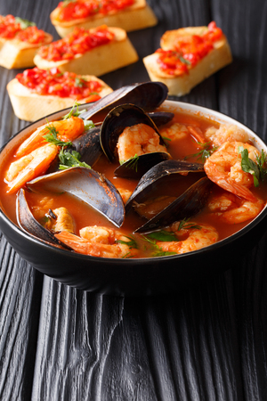Traditional tomato seafood soup with shrimps, fish fillet and mussels closeup in a bowl on the table. vertical 免版税图像