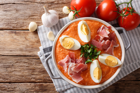 Fresh summer Antequera Porra soup of tomatoes, peppers and garlic served with boiled eggs and ham closeup in a pan on the table. horizontal top view from above