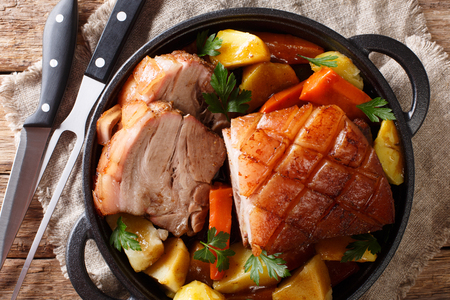 Krustenbraten Pork Roast with Crispy Rind with vegetables close-up in a frying pan on the table. horizontal top view from above Stock Photo - 111330404