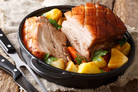 Traditional Bavarian crispy pork Krustenbraten baked in beer with vegetables close-up in a frying pan on the table. horizontal