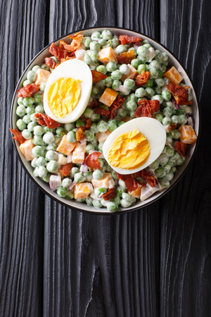 English salad of fresh green peas with eggs, bacon and cheese dressed with cream sauce close-up in a bowl on the table. Vertical top view from above