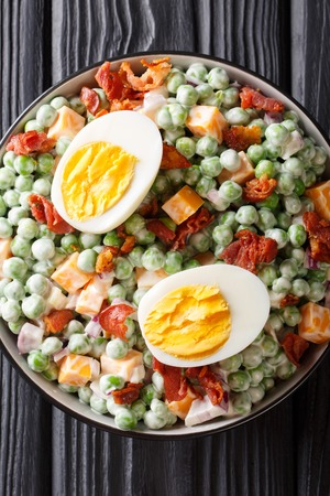Easy English salad of raw green peas with boiled eggs, bacon and cheddar cheese with sauce close-up in a bowl on the table. Vertical top view from above