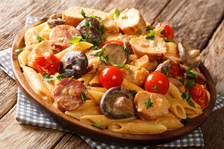 penne with grilled chicken, wild mushrooms, smoked sausage, tomatoes and creamy cheese sauce close-up on a plate on the table. horizontal