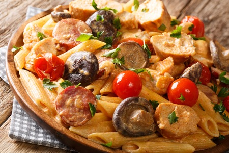 Delicious hearty pasta penne with chicken, wild mushrooms, smoked sausage with creamy cheese sauce close-up on a plate on the table. horizontal 免版税图像