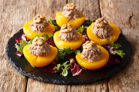 Ripe peach halves stuffed with canned tuna and walnuts, served with leafy lettuce close-up on the table. horizontal Stock Photo