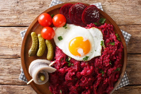 traditional Labskaus recipe of potato, corned beef and beet with a fried egg and herring close-up on a plate on the table. horizontal top view from above