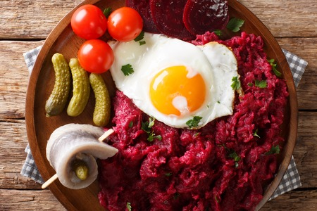 Labskaus is a traditional northern dish of potatoes, corned beef and beets with fried egg, pickles and herring close-up on a plate on the table. horizontal top view from above