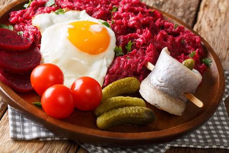 traditional Labskaus recipe of potato, corned beef and beet with a fried egg and herring close-up on a plate on the table. horizontal