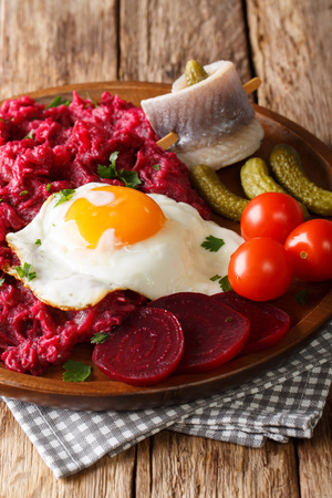 German cuisine Labskaus is a mashed potato, corned beef and beetroot with fried egg, pickled cucumbers and rollmop close-up on a plate. Vertical