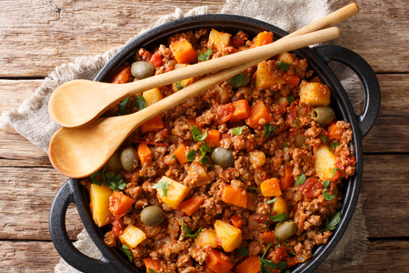 This picadillo recipe is an easy, warm and comforting Mexican dish made from ground beef and potatoes cooked in a flavorful sauce closeup on a pan. Horizontal top view from above Banque d'images