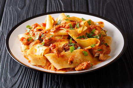 Italian noodles with slow cooked pork in a spicy tomato sauce closeup on a plate on the table. Horizontal Stock Photo
