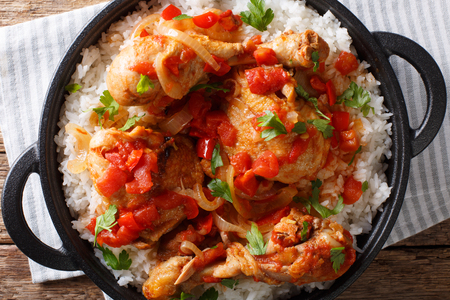 Haitian Chicken Recipe is a one pot of chicken, tomatoes, wine, spices, and rice close-up on the table. Horizontal top view from above