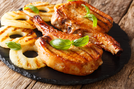 Freshly prepared delicious grilled pork chop in honey pineapple glaze close-up on slate on the table. horizontal