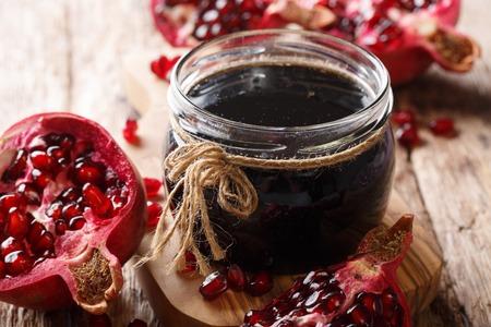Azerbaijani seasoning Narsharab sauce made from pomegranate juice in a jar close-up on the table. horizontal Stock Photo