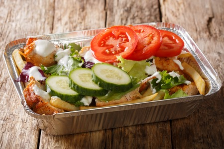 Takeaway Dutch kapsalon from french fries, chicken, fresh salad, cheese and sauce in a close-up foil tray on the table. horizontal