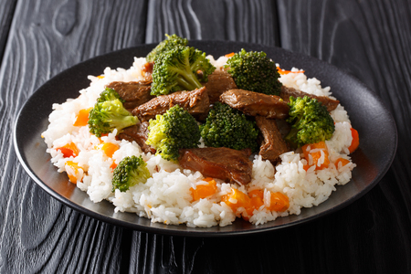 Portion of fried beef with broccoli with rice garnish and persimmon close-up on a plate on the table. horizontal