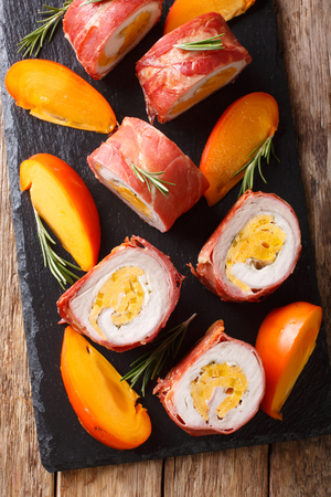 Delicious pork tenderloin stuffed with persimmon and cheese wrapped in prosciutto close-up on the table. Vertical top view from above