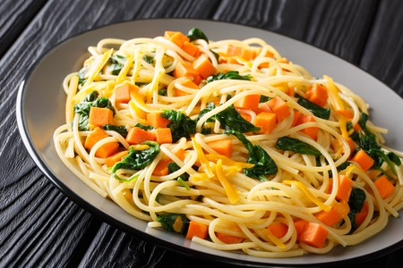 Organic spaghetti meal with pumpkin, spinach and cheddar cheese close-up on a plate on the table. horizontal