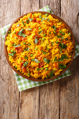 Indian food Tawa Pulao rice with vegetables and spices close-up on a plate. Vertical top view from above Stock Photo