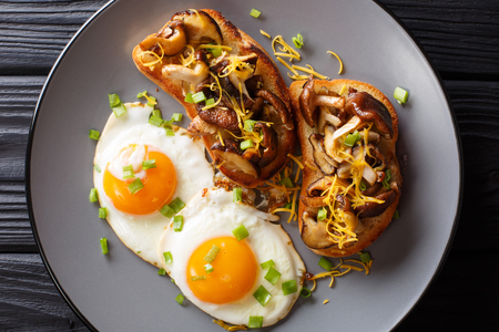 Delicious toast with shiitake mushrooms and cheddar cheese served with fried eggs close-up on a plate on the table. horizontal top view from above