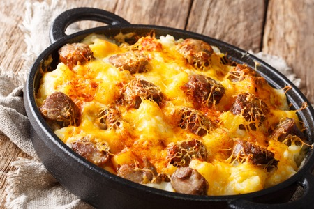 Traditional casserole of potatoes, smoked sausages with cheese sauce close-up in a frying pan on the table. horizontal Foto de archivo