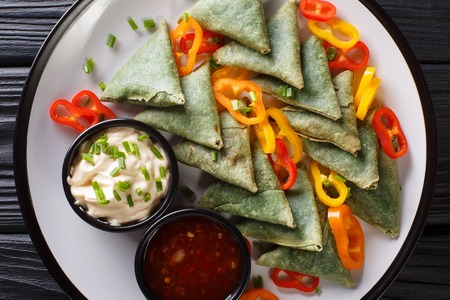 Indian cuisine Spinach samosa served with vegetables and two sauces close-up on a plate on the table. horizontal top view from above Stock Photo