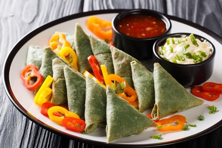 Spinach samosa served with vegetables and two sauces close-up on a plate on the table. horizontal