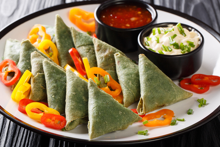 Indian spinach samosa with vegetables and sauces close-up on a plate on the table. horizontal Stock Photo