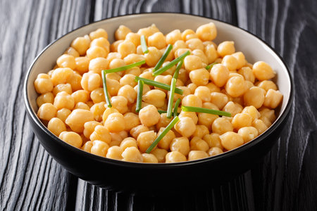 Cooked chickpeas close-up in a black bowl on a wooden table. horizontal background Standard-Bild