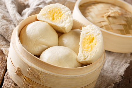 Steamed Chinese bun with custard cream stuff filling in bamboo wooden container on the table. horizontal
