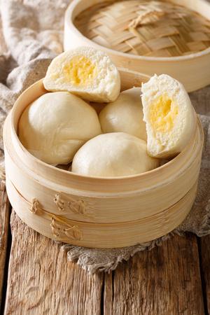 Liu Sha Bao, Salted Egg Yolk Custard Streamed Bun close-up on the table. vertical
