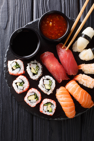 set of Japanese rolls of uramak and nigiri served with two sauces close-up on a slate plate. Vertical top view from above Stok Fotoğraf