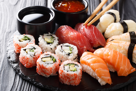 Set of fresh maki, uramaki and nigiri sushi, served on black plate close-up. Horizontal