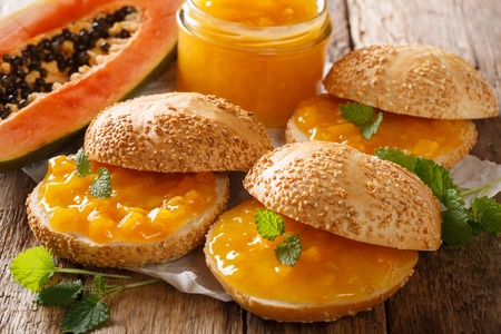 Favorite breakfast sandwiches with fresh papaya jam and mint close-up on the table. horizontal, rustic style