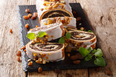 poppy beigli cake with raisins, walnuts decorated with icing and mint close-up on a wooden table. horizontal