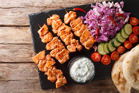 Close-up of chicken skewers with fresh salad, yogurt sauce and pita bread on a slate board. horizontal top view from above Stock Photo