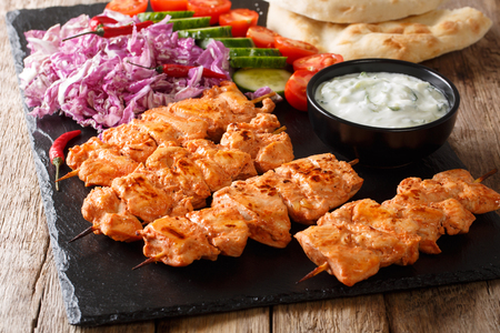 Mediterranean Chicken Kebab with Vegetables, Yogurt Sauce and Pita Bread closeup on a slate board. horizontal