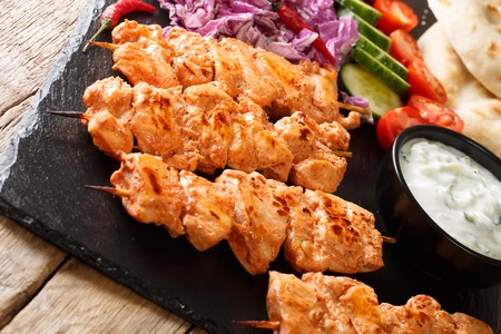 Lebanese Shish Taouk (Tawook)with fresh vegetables, yogurt sauce and pita close-up on the table. horizontal Stock Photo