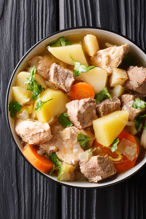 German soup Pichelsteiner or Bismarck stew with vegetables and three kinds of meat close-up in a bowl on the table. Vertical top view from above 写真素材