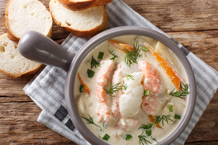 Closeup of creamy fish soup with cod, salmon, carrot and celery in a bowl served with fresh bread on the table. Horizontal top view from above