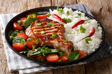 Healthy grilled pork steak with rice and fresh vegetables close-up on a plate on the table. horizontal