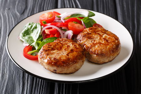 Pittige gebakken gehaktballen crepinette en verse groentesalade close-up op een bord op tafel. horizontaal Stockfoto