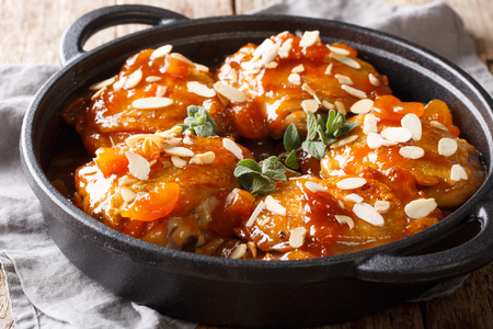 Baked chicken thighs with apricot glaze and almond flakes close-up in a pan on the table. horizontal